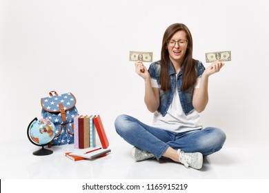 Young upset woman student crying holding dollar bills cash money have financial problem sit near globe, backpack school books isolated on white background. Education in high school university college