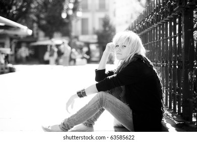 Young urban blond girl staring at camera on urban background