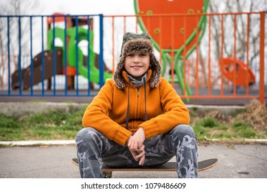 Young urban boy sitting on his skateboard on the street, waiting his friends, looking to camera
