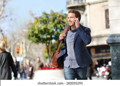Young urban businessman on smart phone running in street talking on smartphone smiling wearing jacket and leather laptop bag on Passeig de Gracia, Barcelona, Catalonia, Spain.