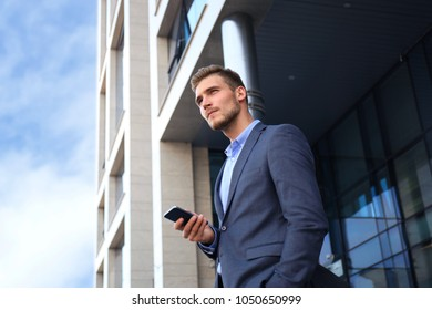 Young urban businessman professional on smartphone walking in street using mobile phone.