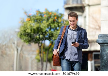 Young urban businessman professional on smartphone walking in street using mobile phone app texting sms message on smartphone wearing smart casual jacket. City lifestyle commute person walking.