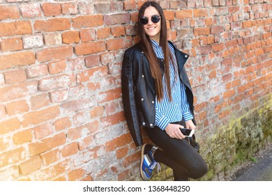 young urban girl in front of brick wall