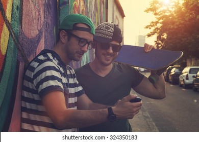 Young urban guys using a smartphone outdoors.