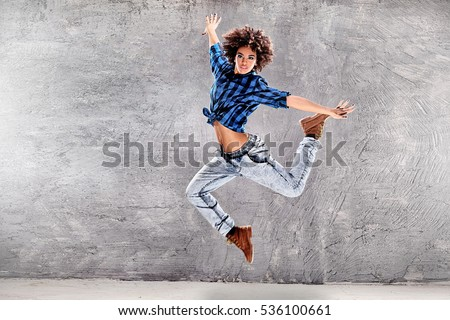 Young urban hip hop dancer jumping and dancing with grunge concrete wall  background. Girl with 4ad0d98295e