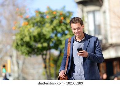 Young urban professional man using smart phone. Businessman holding mobile smartphone using app texting sms message wearing jacket on Passeig de Gracia, Barcelona, Catalonia, Spain.