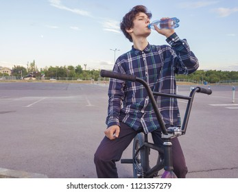 young urban street rider drinking water against the sky