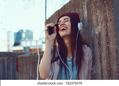 Young urban woman listens to music via headphones and smartphones