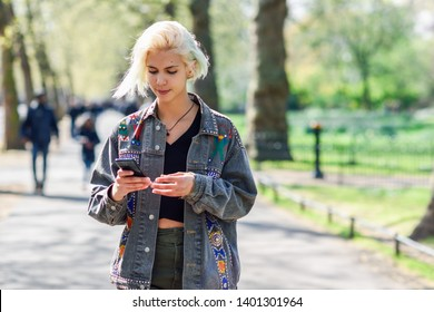 Young urban woman with modern hairstyle using smartphone walking in street in an urban park in London, UK.