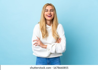 Young Uruguayan blonde woman over isolated blue background keeping the arms crossed in frontal position