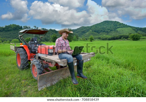 The young US farmer saw the productivity growth that stood on the tractor in the background, rice fields and the sky.