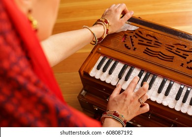 A young Vaishnava woman is playing Indian Traditional Musical Instruments for kirtan harmonium