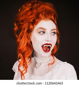 Young vampire woman with long curly hair, pale skin in a white dress on a black background. A beautiful redhead model with red lips. Outfit for halloween. Vampire with open mouth and fangs