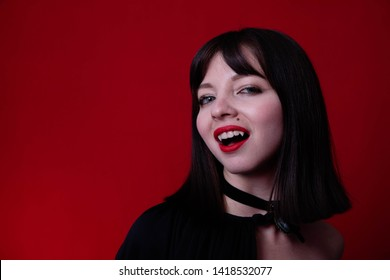 Young vampire woman with short hair, pale skin in a black dress on a red background