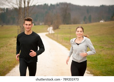 Young  veautiful couple runs on a path in park on autumn afternoon
