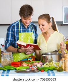 Young vegetarian couple cooking healthy dinner with new recipe at home kitchen