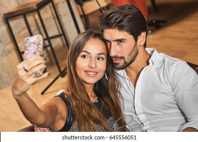 Young very beautiful couple taking selfie in restaurant