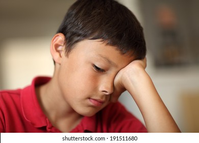 Young very bored student boy with hand covering his eye - very shallow depth of field with copy space