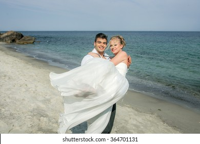 a young and very happy couple running at the beach, wedding at the sea, beautiful white wedding dress