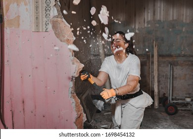 Young very strong and tough woman in white working outfit clothes hitting hard and breaking a wall with a large heavy hammer  during manly renovation work and pieces of the wall flying away