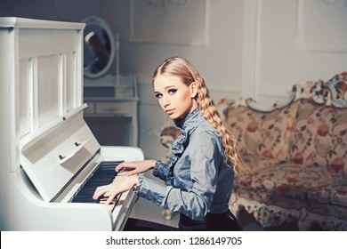 Young Victorian lady in a tender blue dress playing piano. Lovely blond woman sitting in room with vintage furniture. Home education concept.