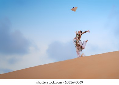 Young Vietnam woman wearing Ao Dai culture traditional jumping on the desert at Muine in Vietnam,vintage style,travel and relaxing concept.