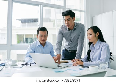 Young Vietnamese businessman showing his idea on laptop screen to coworkers
