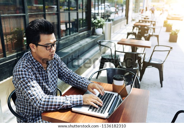 Young Vietnamese businessman working on laptop in outdoor cafe