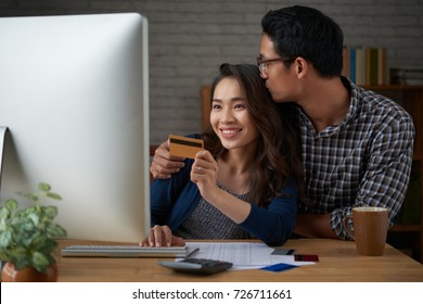 Young Vietnamese couple making online purchases at home
