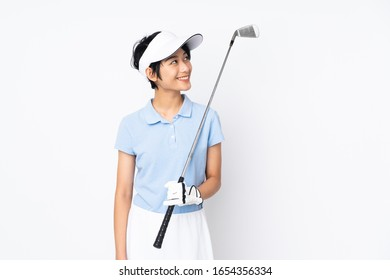 Young Vietnamese golfer woman over isolated white wall looking up while smiling