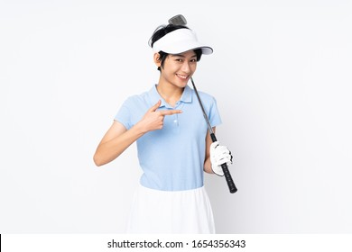 Young Vietnamese golfer woman over isolated white wall playing golf and pointing to the lateral