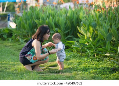 Young Vietnamese mother help her son start walking. Mother teach her son, bring up, take care him.