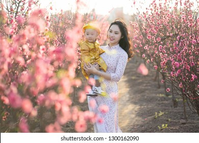 Young Vietnamese mother with her son in traditional costume in peach flower garden