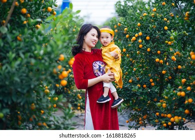 Young Vietnamese mother with her son in traditional costume in Kumquat garden