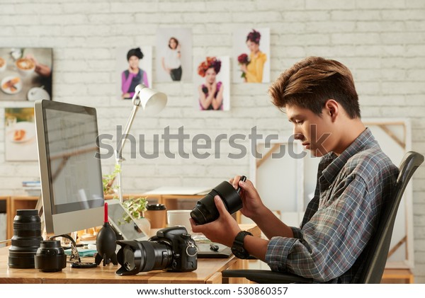 Young Vietnamese photographer cleaning lenses in his studio