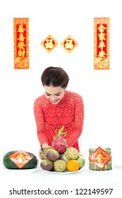 Young Vietnamese preparing festive table with fruit basket and traditional rice cake for Tet