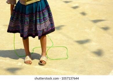 Young Vietnamese schoolgirl stands in courtyard with jumprope.