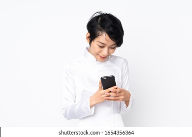 Young Vietnamese woman with short hair wearing a traditional dress over isolated white background sending a message with the mobile