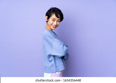 Young Vietnamese woman with short hair over isolated purple background looking to the side and smiling