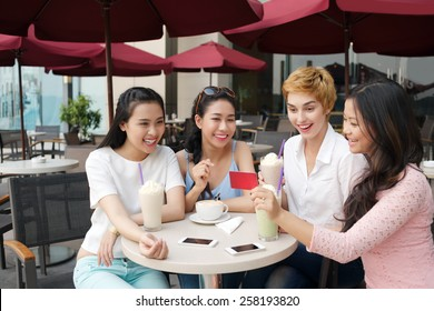 Young Vietnamese woman showing gift card to her friends in a cafe