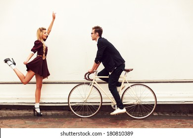 Young vintage hipster pretty couple having fun outdoor in summer on the street in city with cool bicycle behind white wall. Man with girl in spring urban style