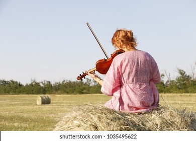 Young violinist seating on the sheaf in the wheat field and playing violin, captured from back side in pink dress