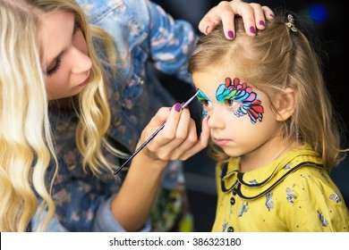 Young visagist painting the face of a little girl