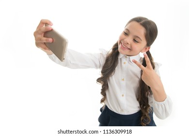 Young vlogger stream online. Child school uniform smart kid happy face. Girl cute long curly hair holds smartphone taking selfie white background. Child girl school uniform clothes holds smartphone.