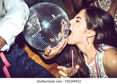 Young vogue woman with eyes closed holding drink and biting disco ball during glamorous party.