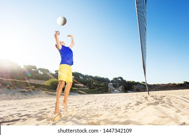 Young volleyball player jump serving on the beach