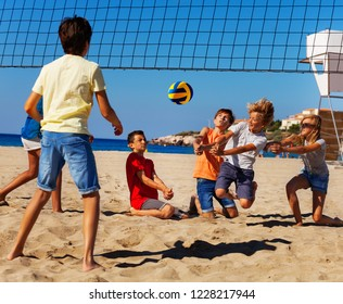 Young volleyball players in action on sand court