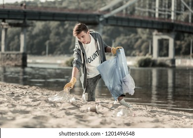 Young volunteer. Young dark-haired volunteer wearing sport suit spending his day cleaning the sand on the beach