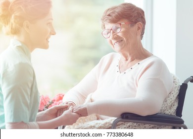 Young volunteer holding hands of smiling elderly woman in a wheelchair