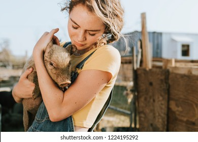 Young volunteer with a piglet, The Sanctuary at Soledad, Mojave